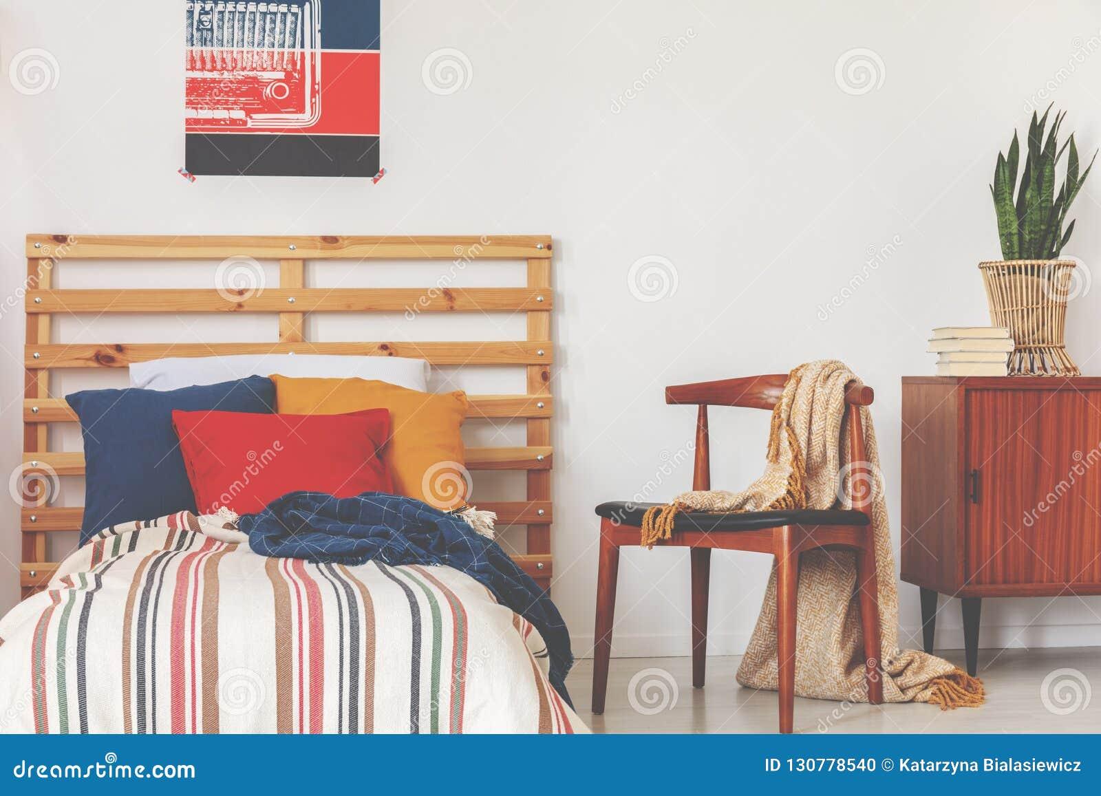 Almohadas azules, rojas y anaranjadas en sola cama con el edredón pelado y el cabecero de madera en el interior del dormitorio de