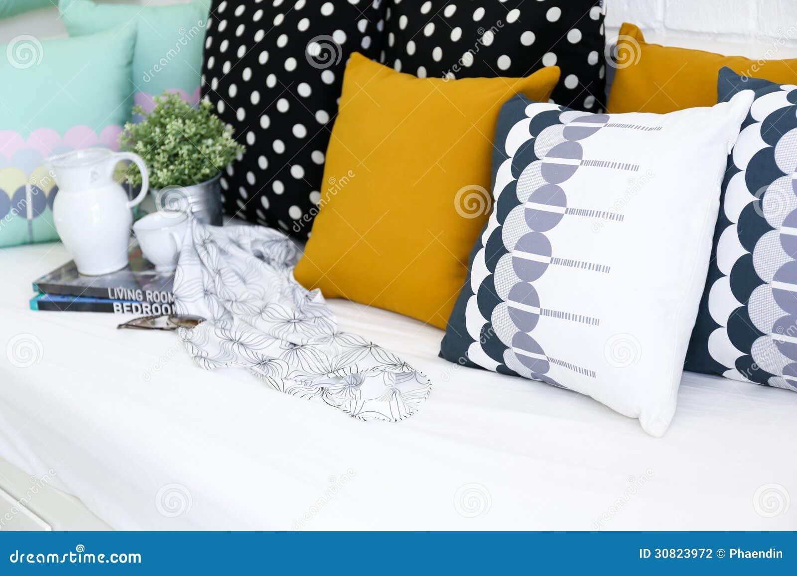Almohadas coloridas en un sofá con la pared de ladrillo blanca i