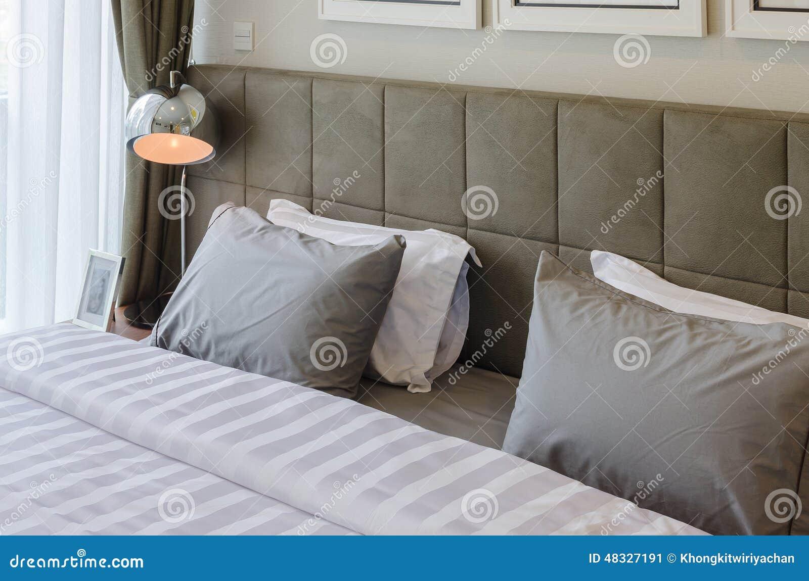 Almohadas grises en cama con la l mpara moderna imagen de - Almohadas para cama ...
