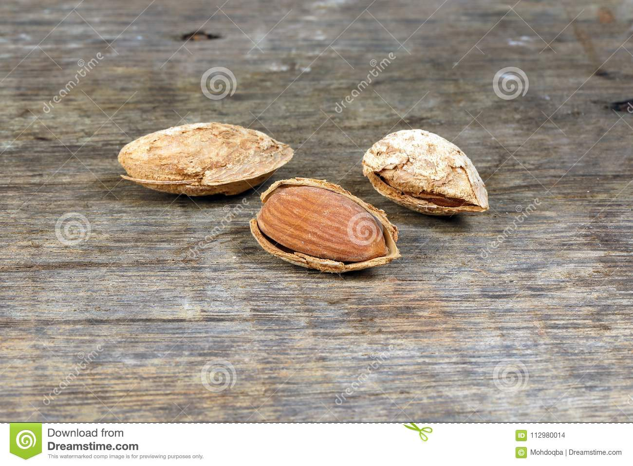 Almond nut in shell on rustic wood