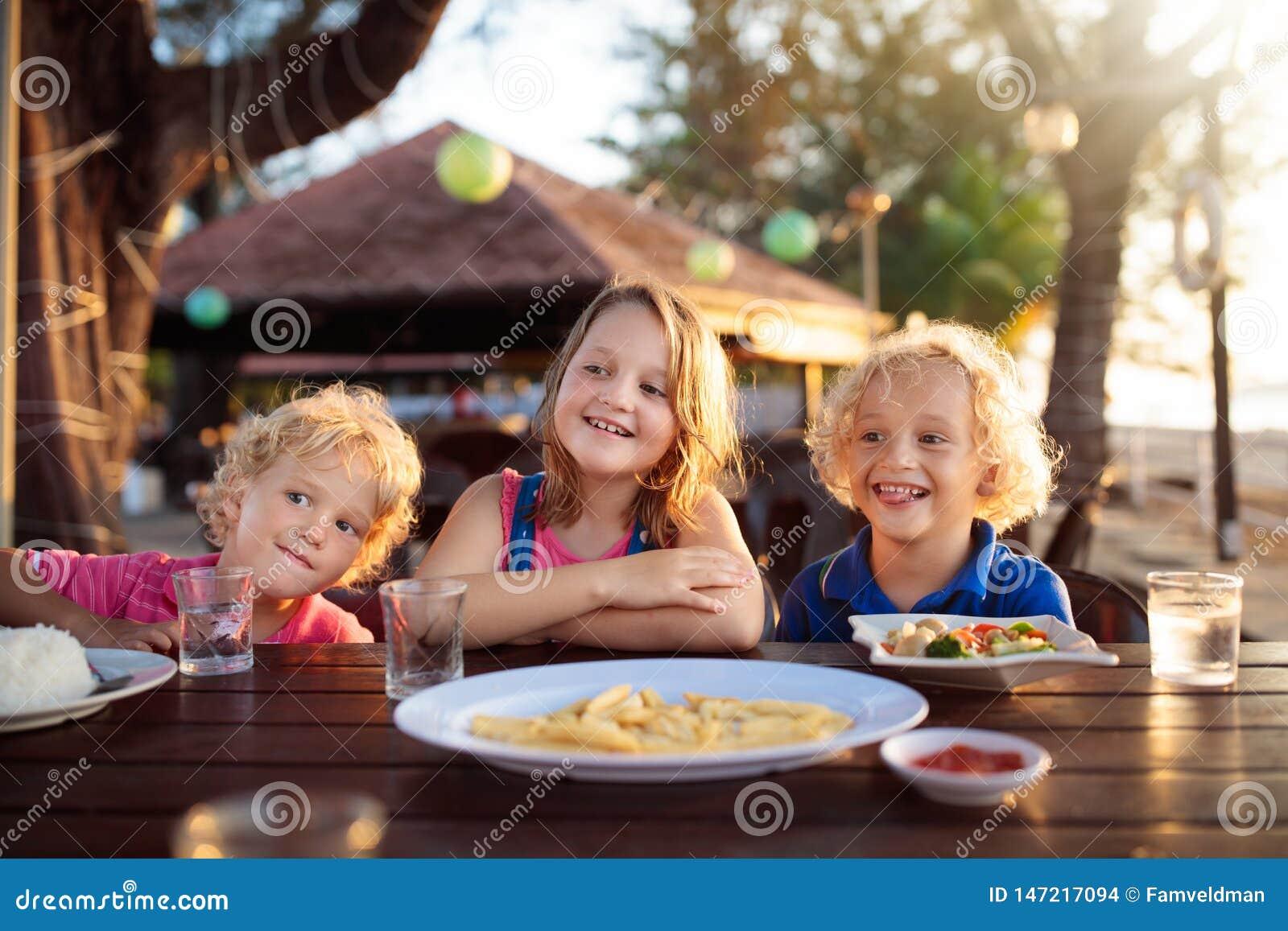 Almuerzo de las vacaciones de familia Ni?os en restaurante de la playa
