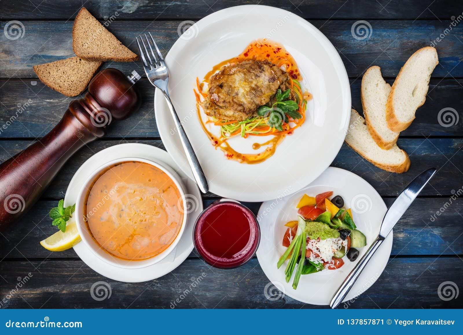 Almuerzo determinado típico Tajada del pollo, sopa de la calabaza y ensalada de las verduras, servidas con los cubiertos
