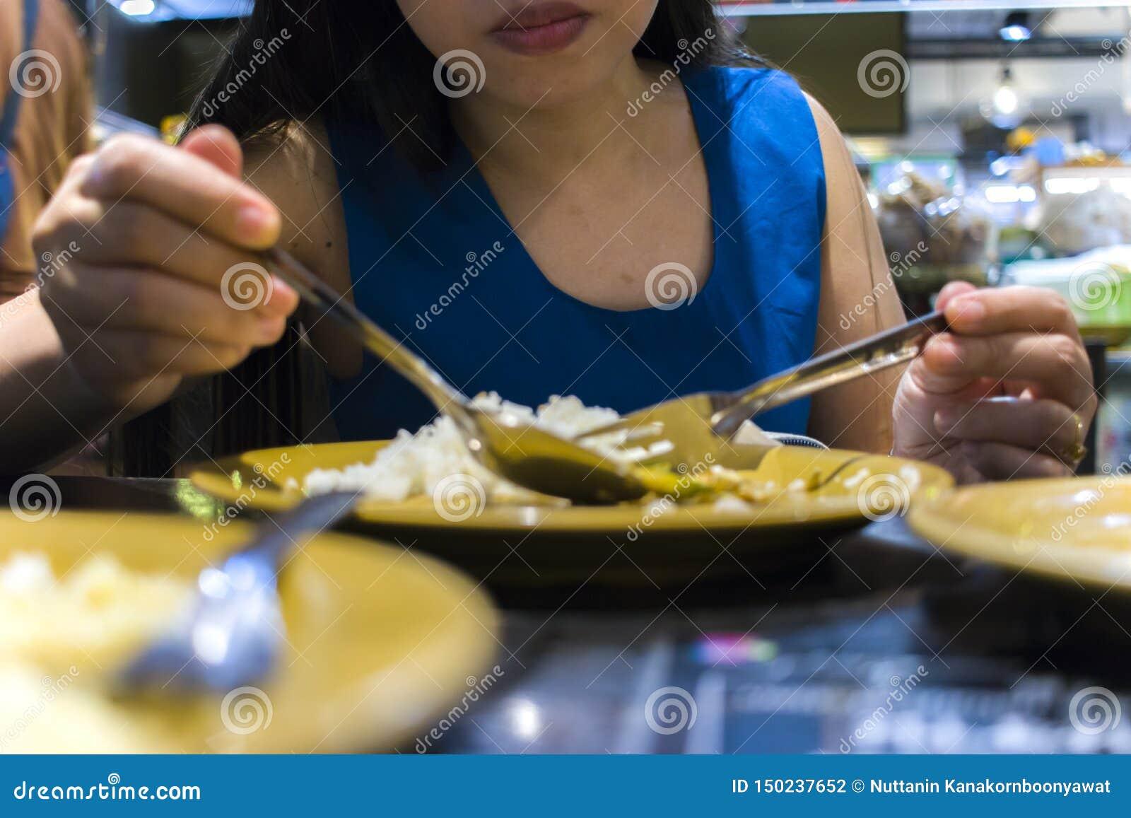 Almuerzo en un restaurante tailandés Una mujer come el arroz con las verduras y la sopa
