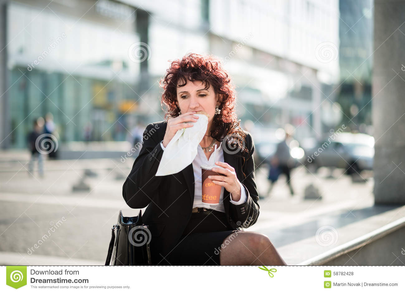 Almuerzo rápido - mujer de negocios que come en calle