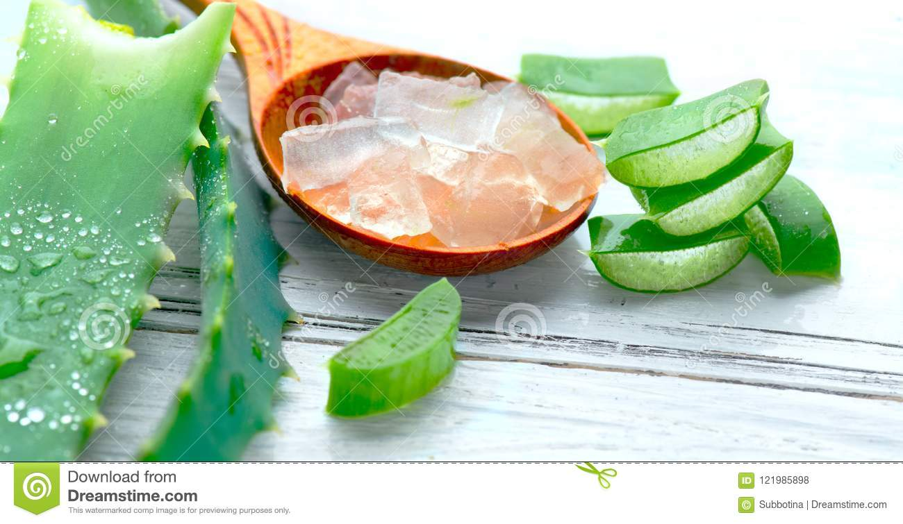Aloe Vera gel closeup on white wooden background. Organic sliced aloevera leaf and gel, natural organic cosmetic ingredients