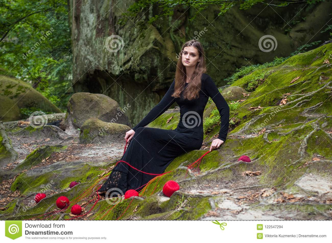 Alone beautiful girl is sitting on green moss in a fairy forest