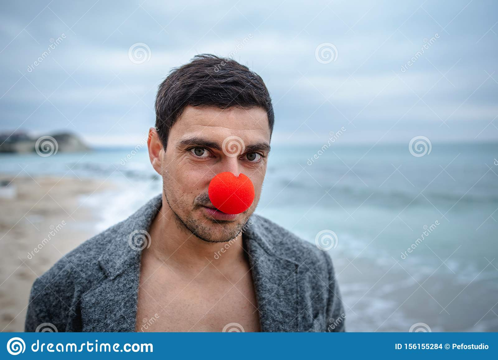 Alone Man With A Red Nose On The Beach Stock Photo
