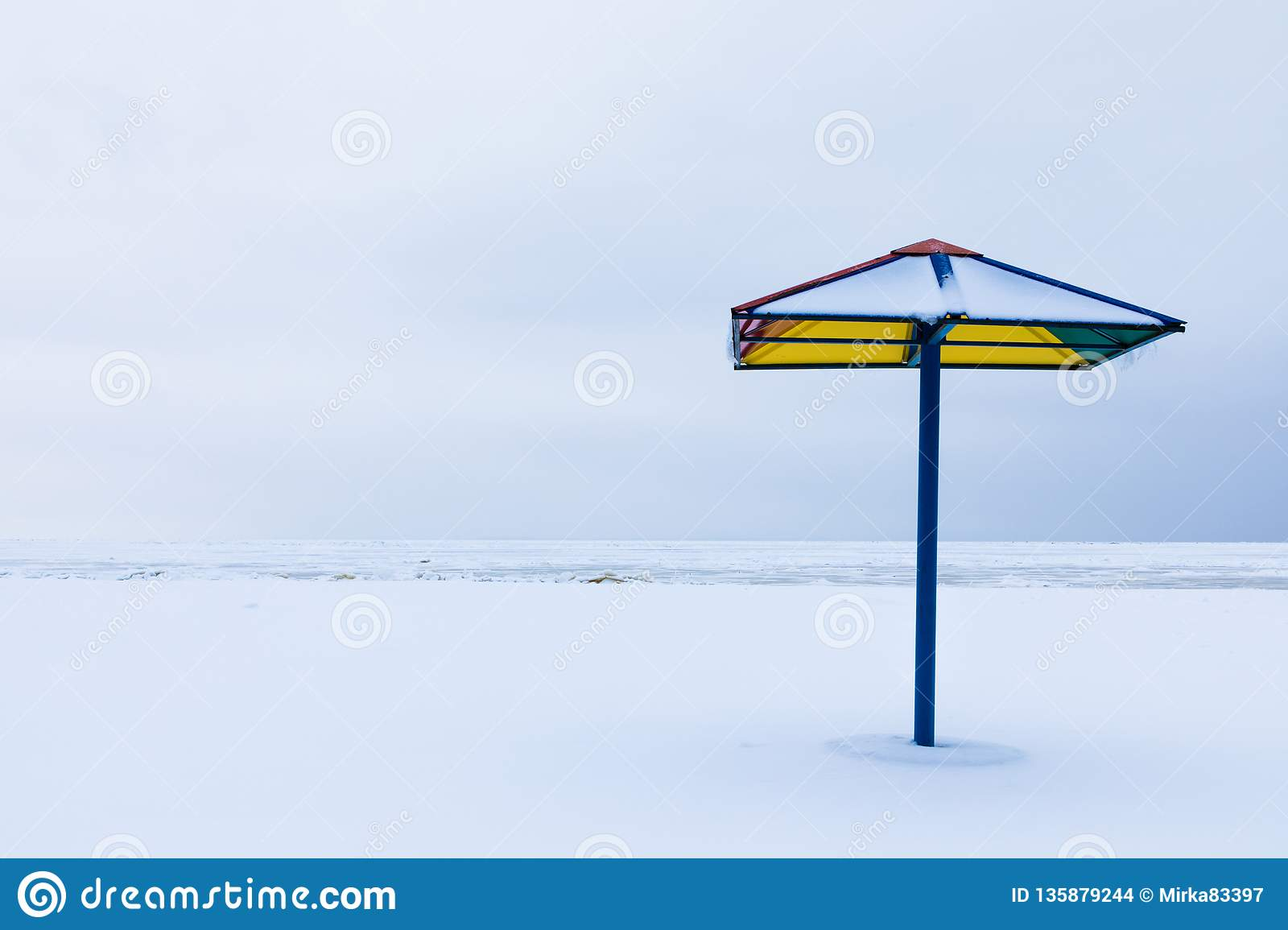 The alone sunshade or the parasol on the winter beach under the snow