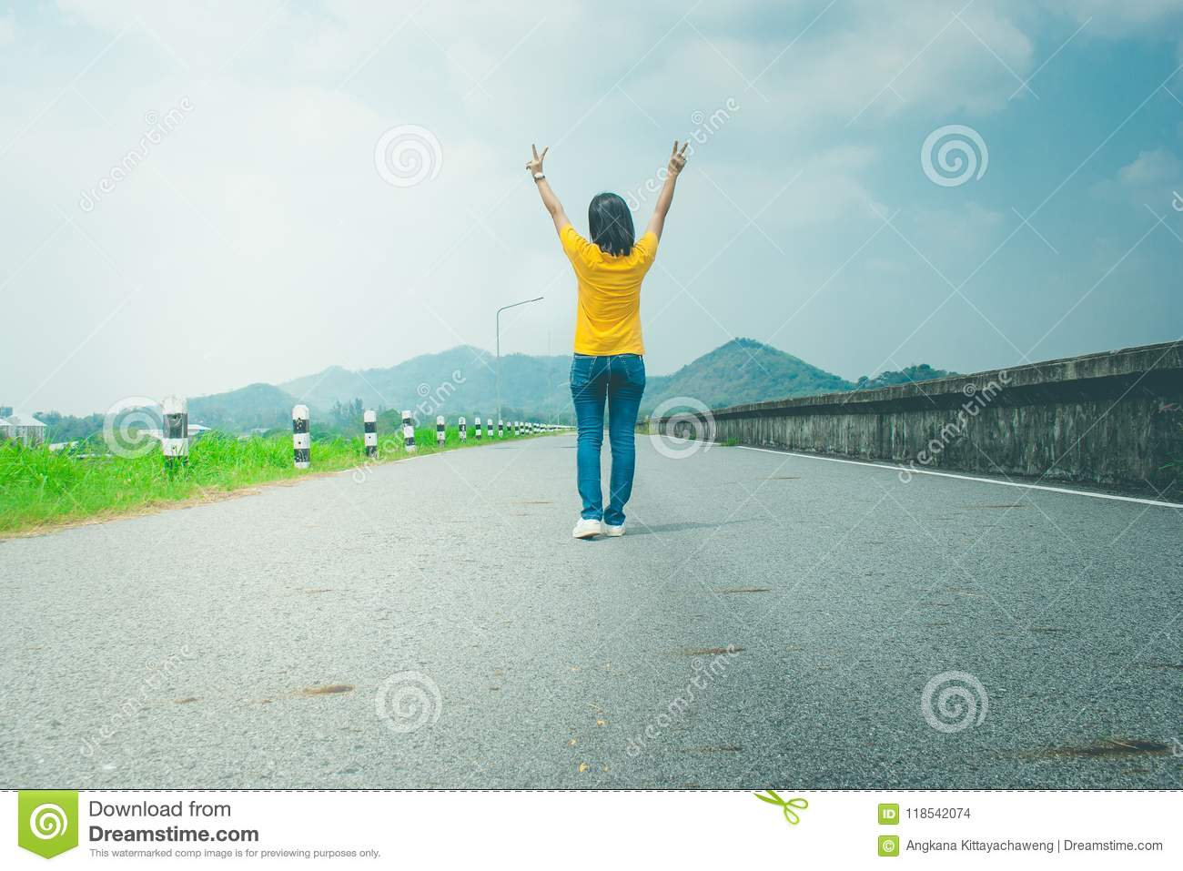 Alone woman traveler or backpacker walking along countryside road along side with reservoir, she raise hands over head.