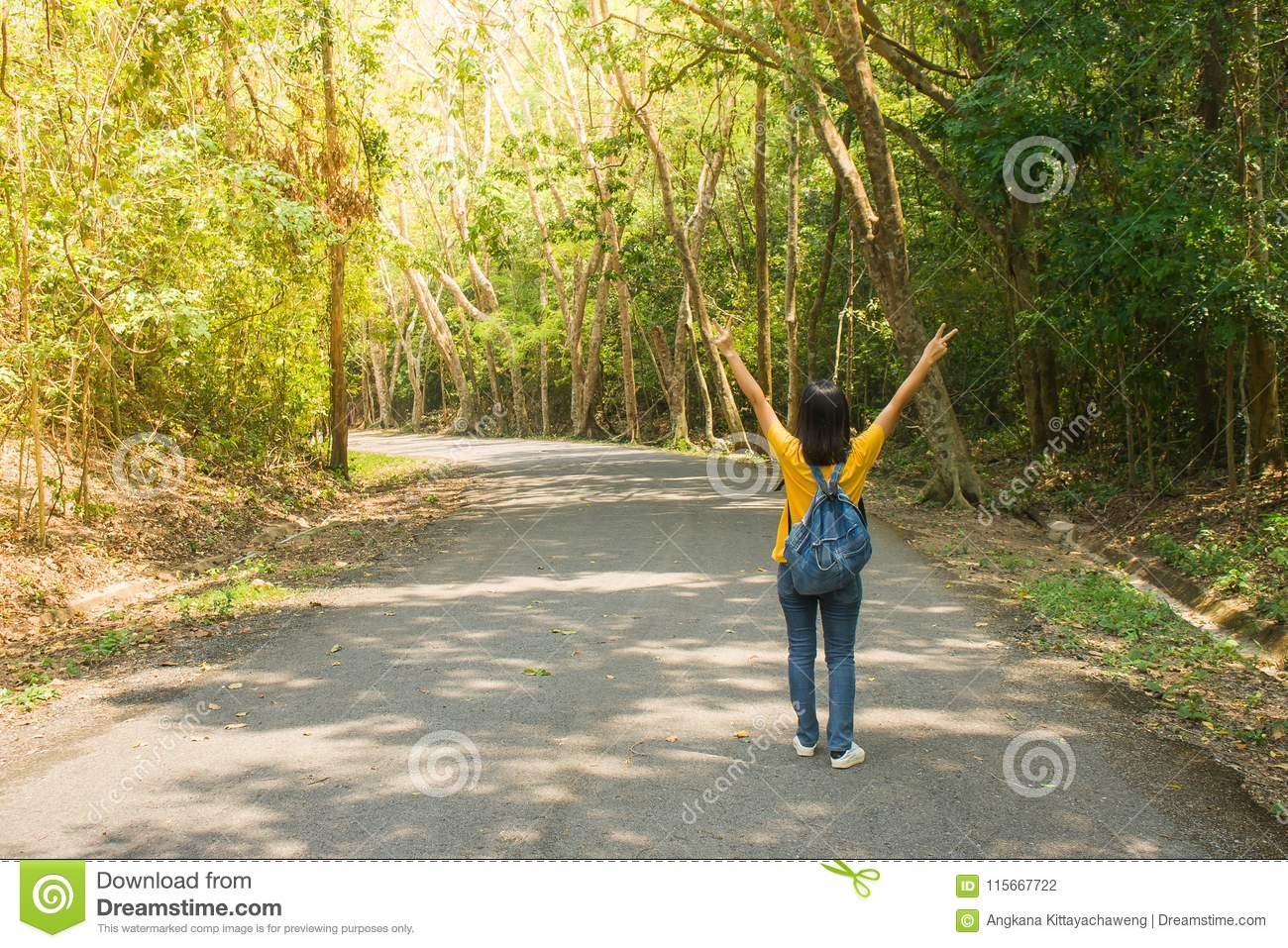 Alone woman traveller or backpacker walking along contryside road among green trees, she has feeling happiness.