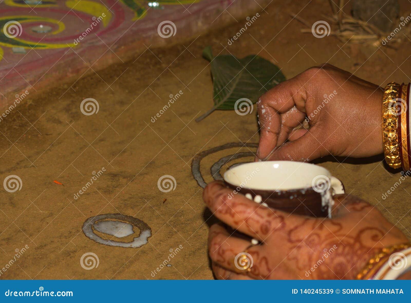 Alpana & x28; Pittura bianca con riso-Paste& liquido x29; sta dipingendo in una cerimonia di nozze del bengalese