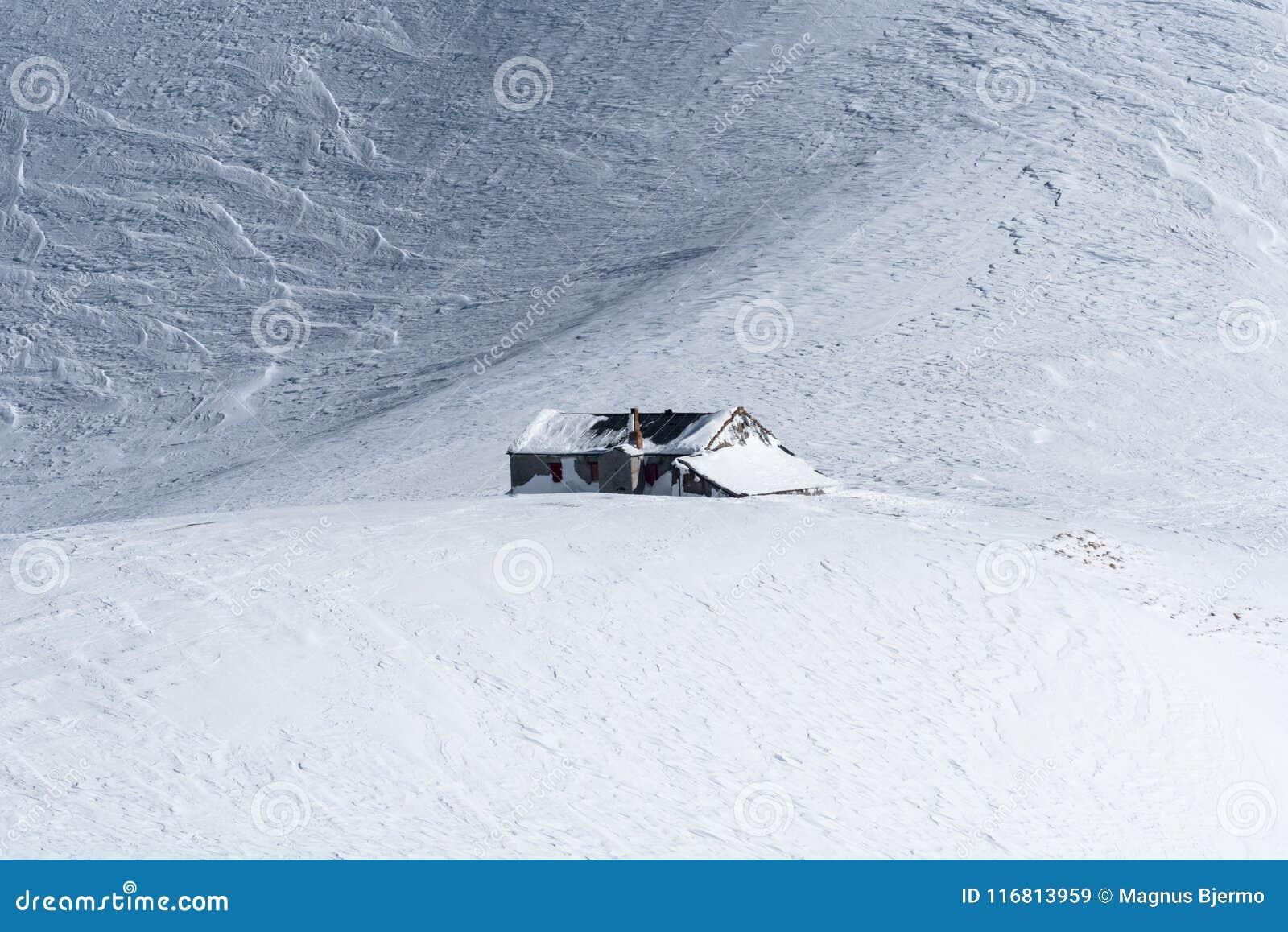 Alpine mountain hut isolated on windpacked snow field