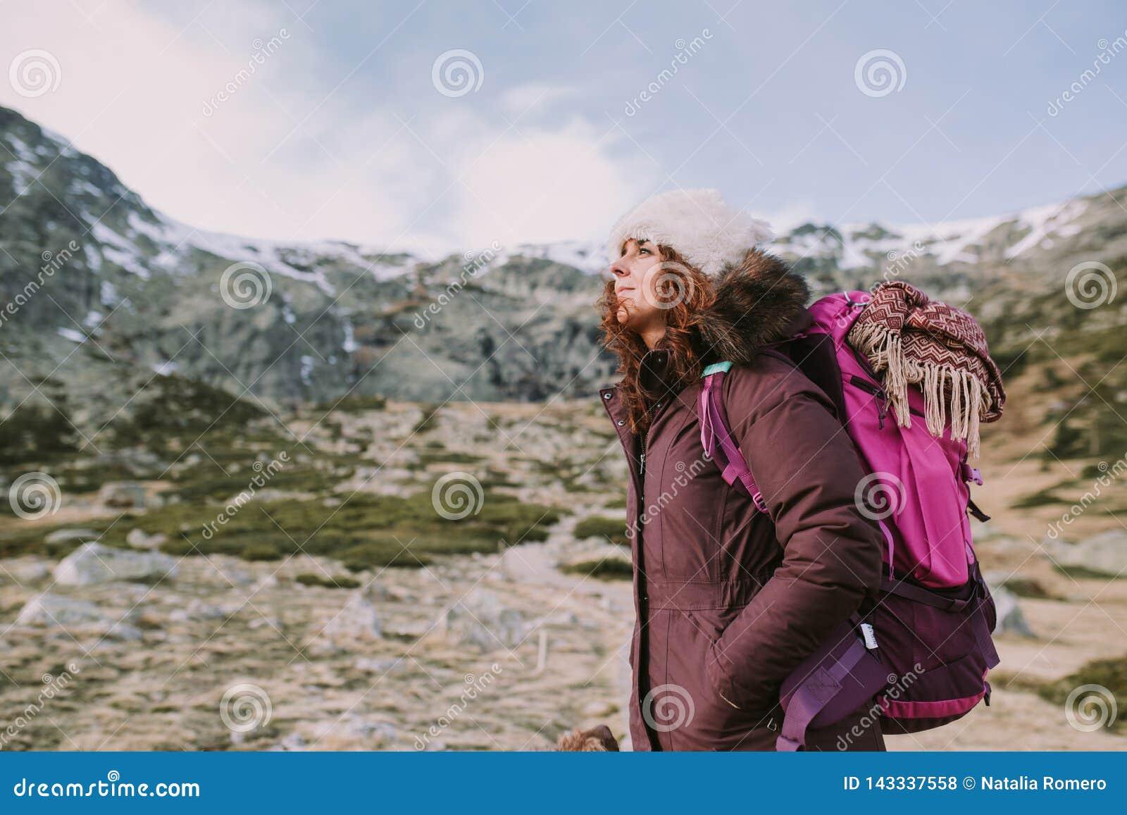 Alpinista dziewczyna z plecakiem na ona z powrotem spojrzenia wokoło wysokich wzgórzy i zielonych łąk