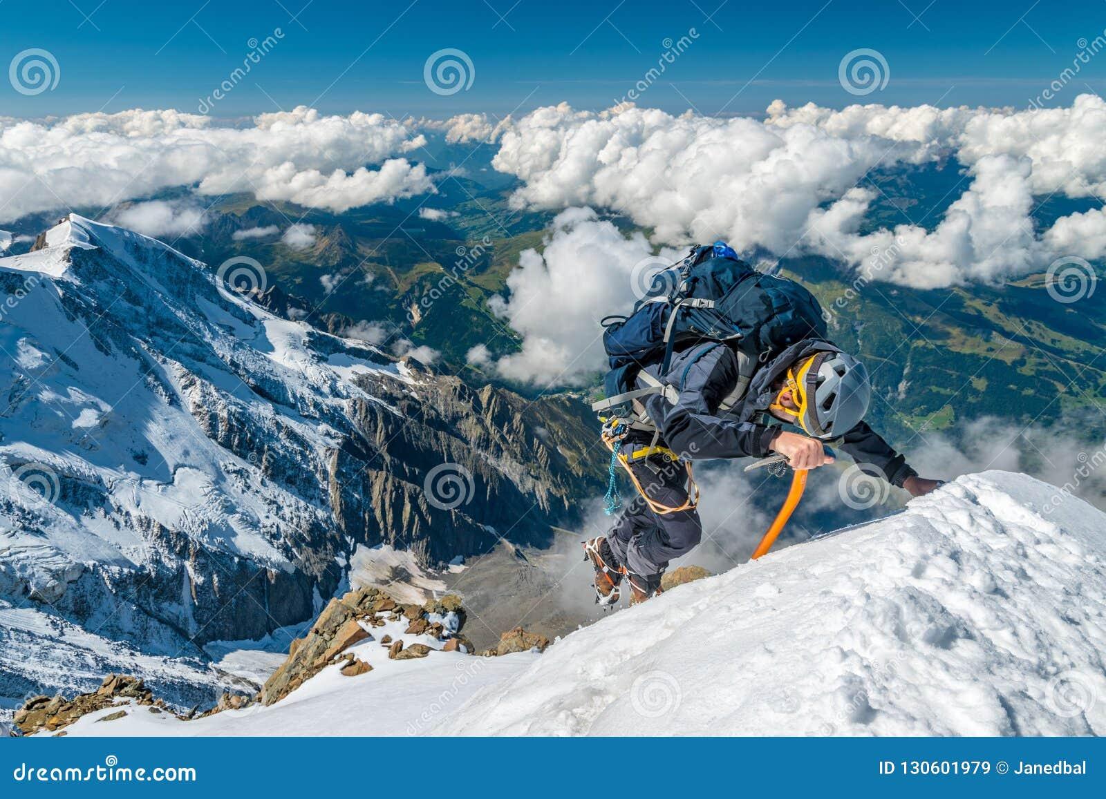 Alpinista extremo na alta altitude na cimeira da montanha de Aiguille de Bionnassay, maciço de Mont Blanc, cumes, França