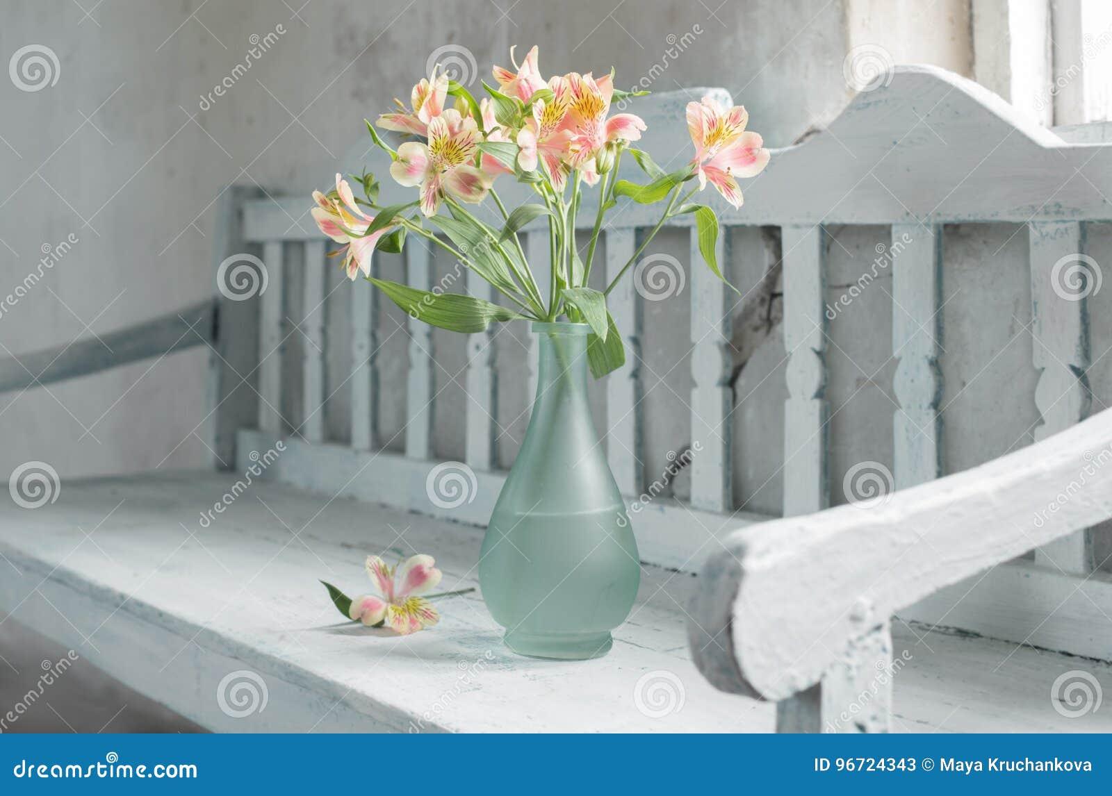 Alstroemeria in vase on old wooden bench