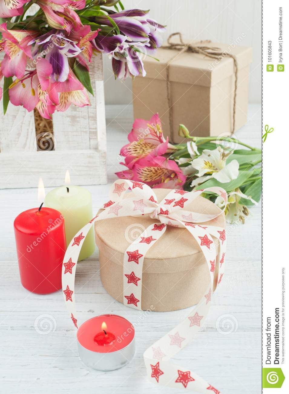 alstromeria flowers in the wooden box lit candle stock image