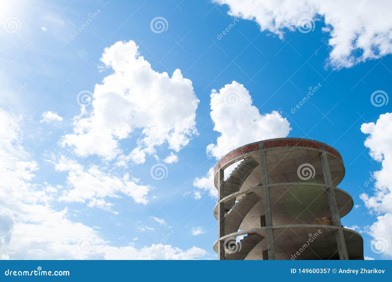 Alta costruzione concreta contro il cielo blu e le nuvole bianche