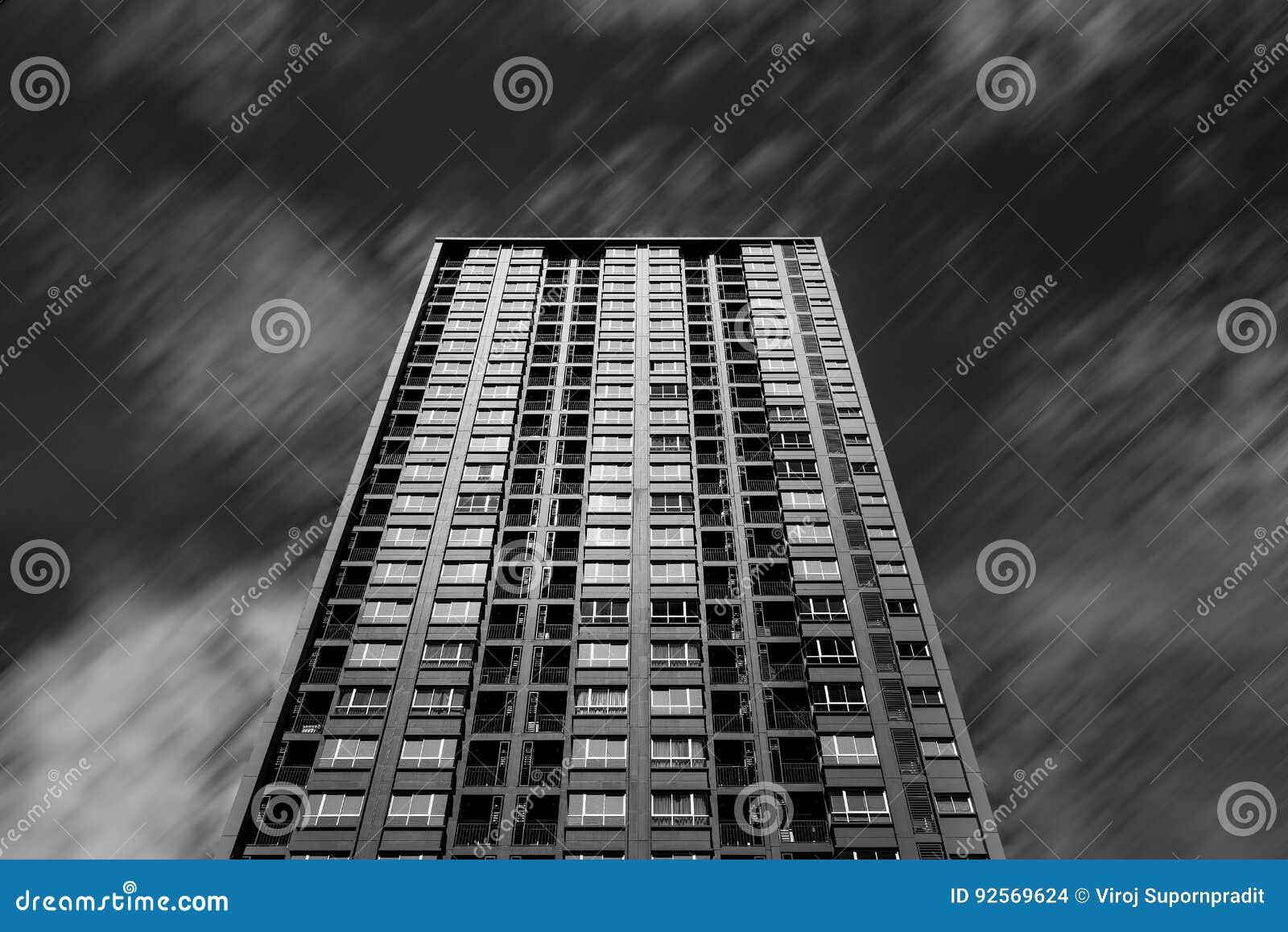 Alta costruzione e nuvola corrente in bianco e nero per fondo