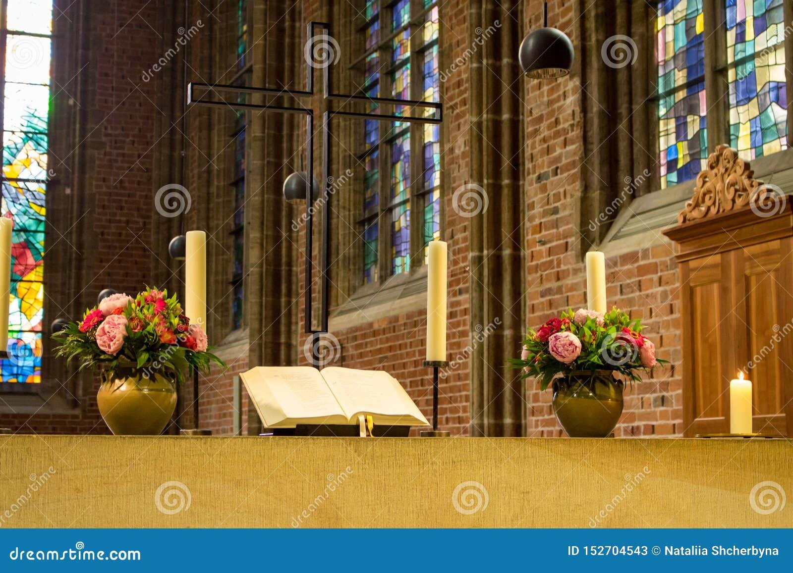 Altar bonito na catedral católica A Bíblia Sagrada aberta com flores, velas e cruz Decoração elegante da igreja