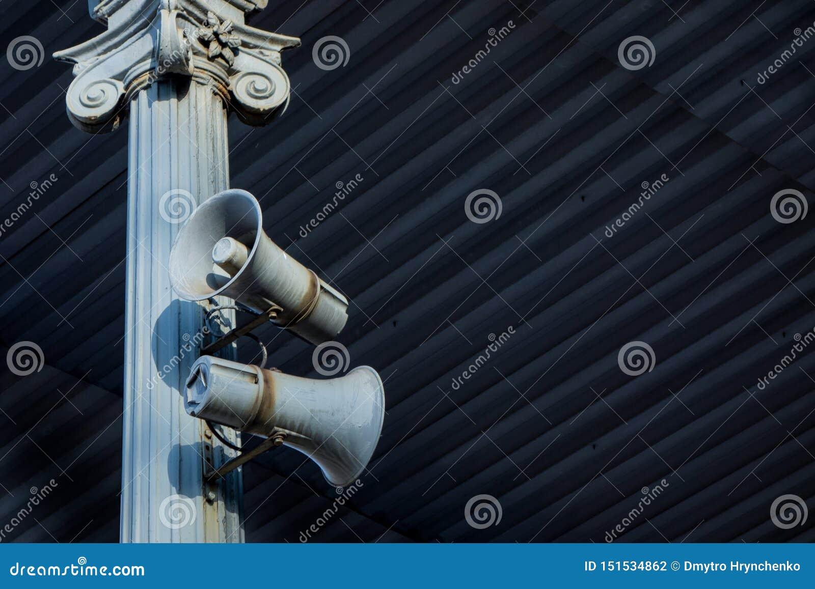 Altavoz de la carga de dos cuernos en el marco metálico antiguo de la columna debajo de la techumbre Sistema industrial o del tra