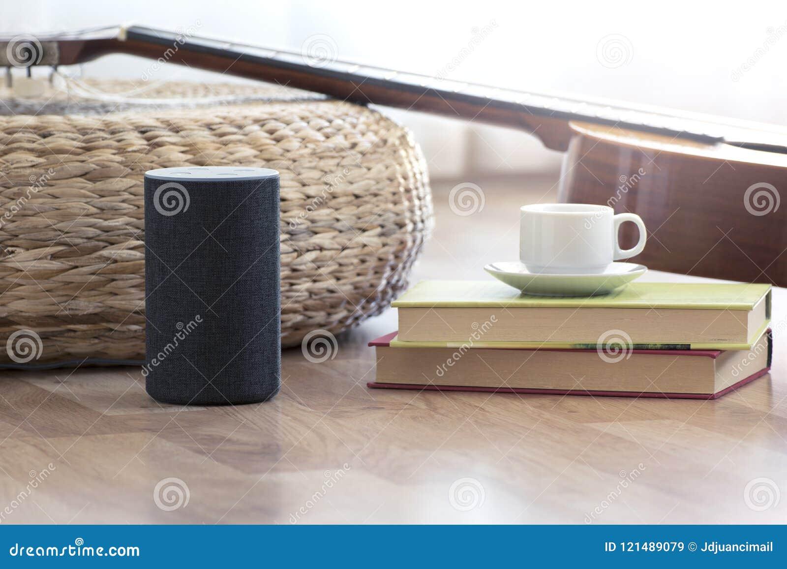 Altavoz del ayudante personal en un piso de madera de una sala de estar casera elegante Después, una guitarra y algunos libros y