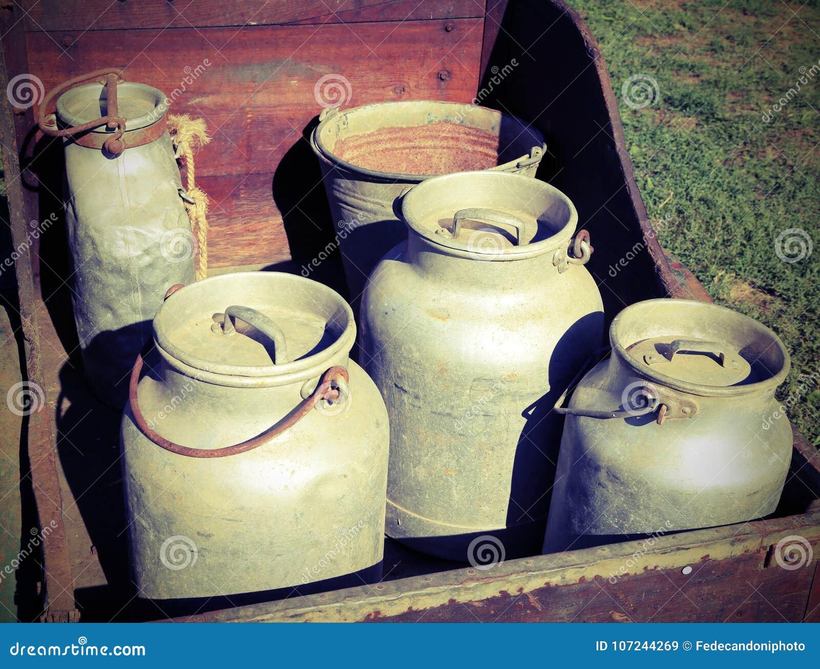 Alte Aluminiummilchdosen zum Transport der frischen Milch in einem hölzernen c