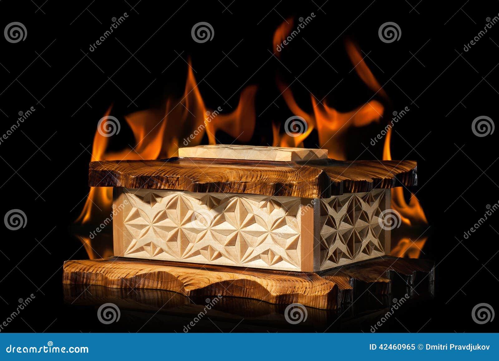 Alte braune hölzerne Schatulle in der Feuerflamme auf schwarzem Hintergrund
