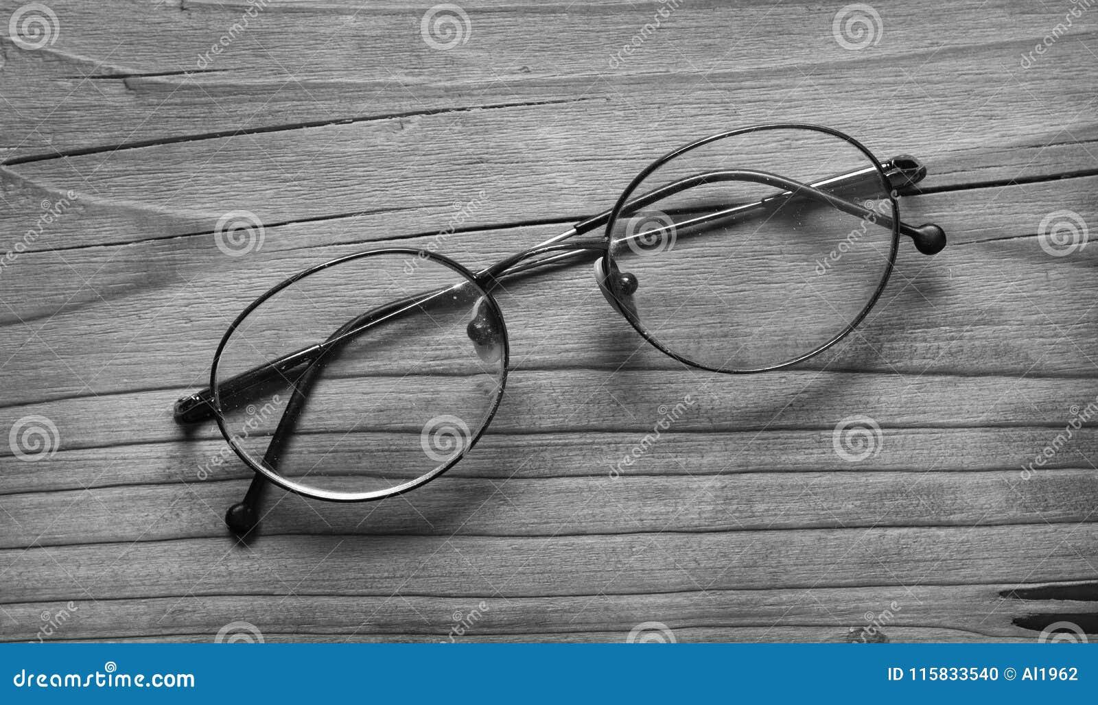 Alte Brillen auf dem Holztisch - Schwarzweiss