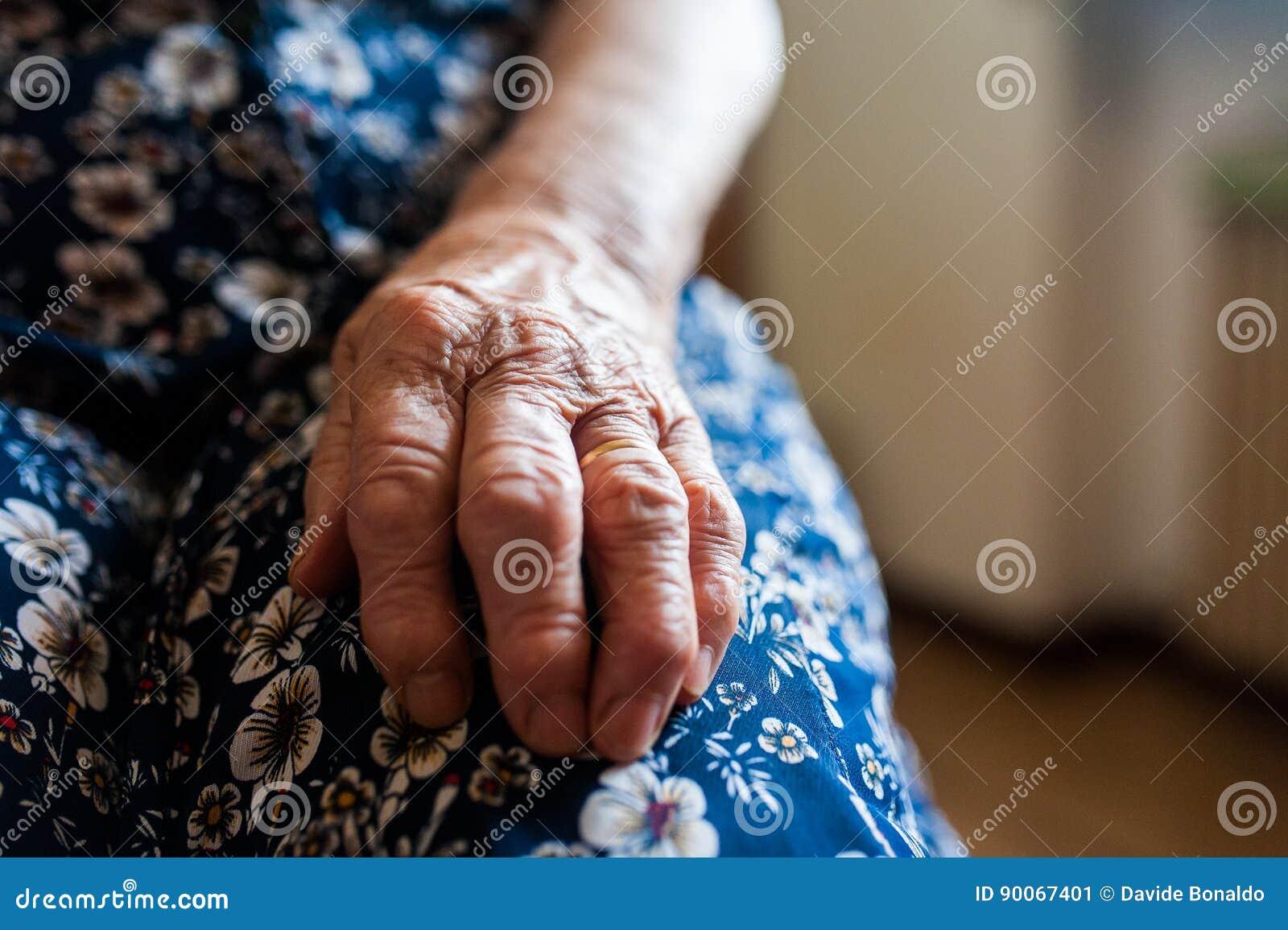Alte Dame ` s Hand mit Falten und nahem hohem des Eherings