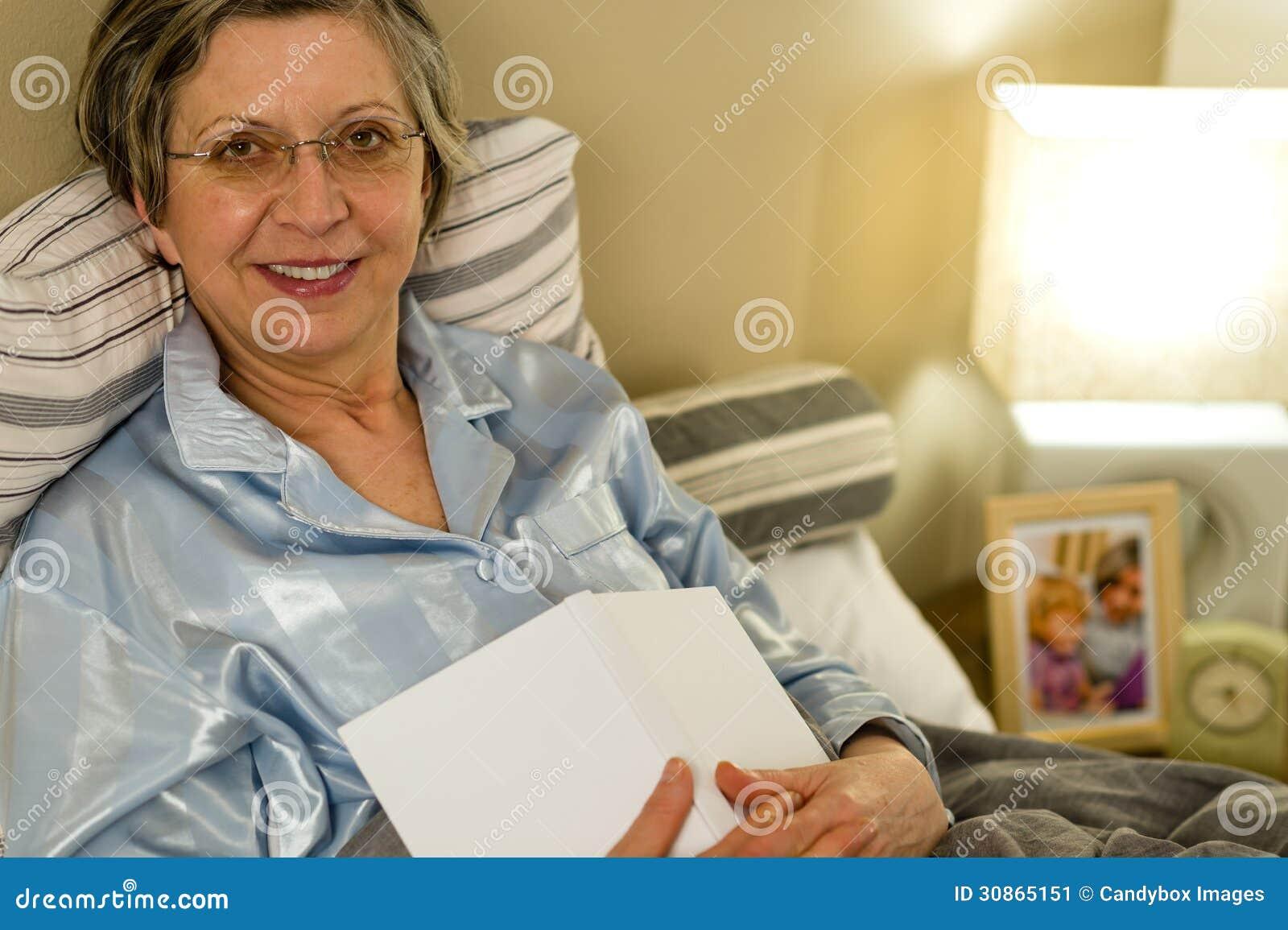 alte frau in den pyjamas die im bett liegen stockbild bild. Black Bedroom Furniture Sets. Home Design Ideas