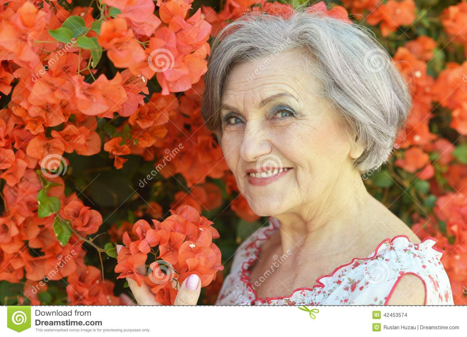 Alte Frau mit roten Blumen