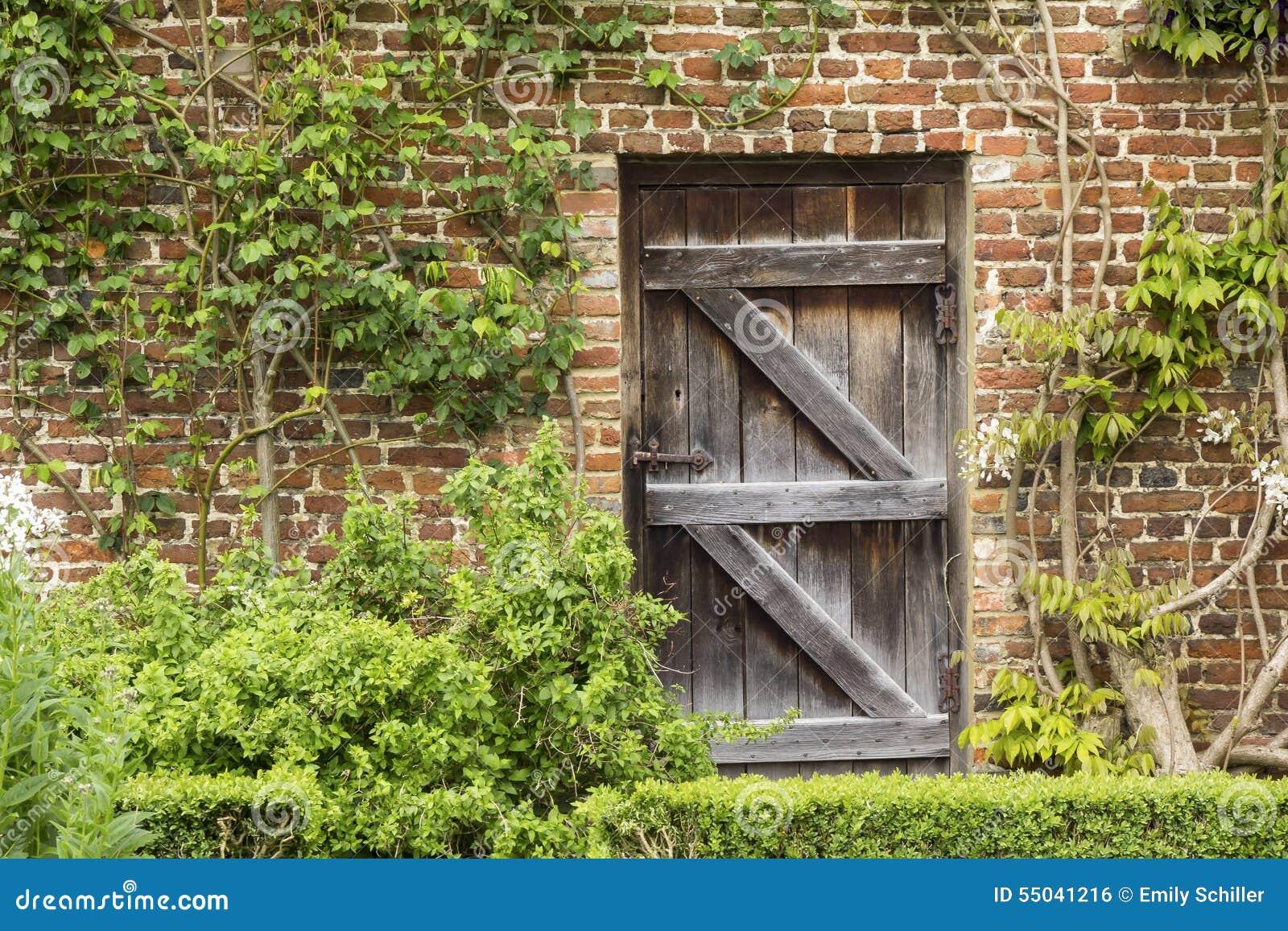 Alte geschlossene Holztür in einer Backsteinmauer in einem Garten