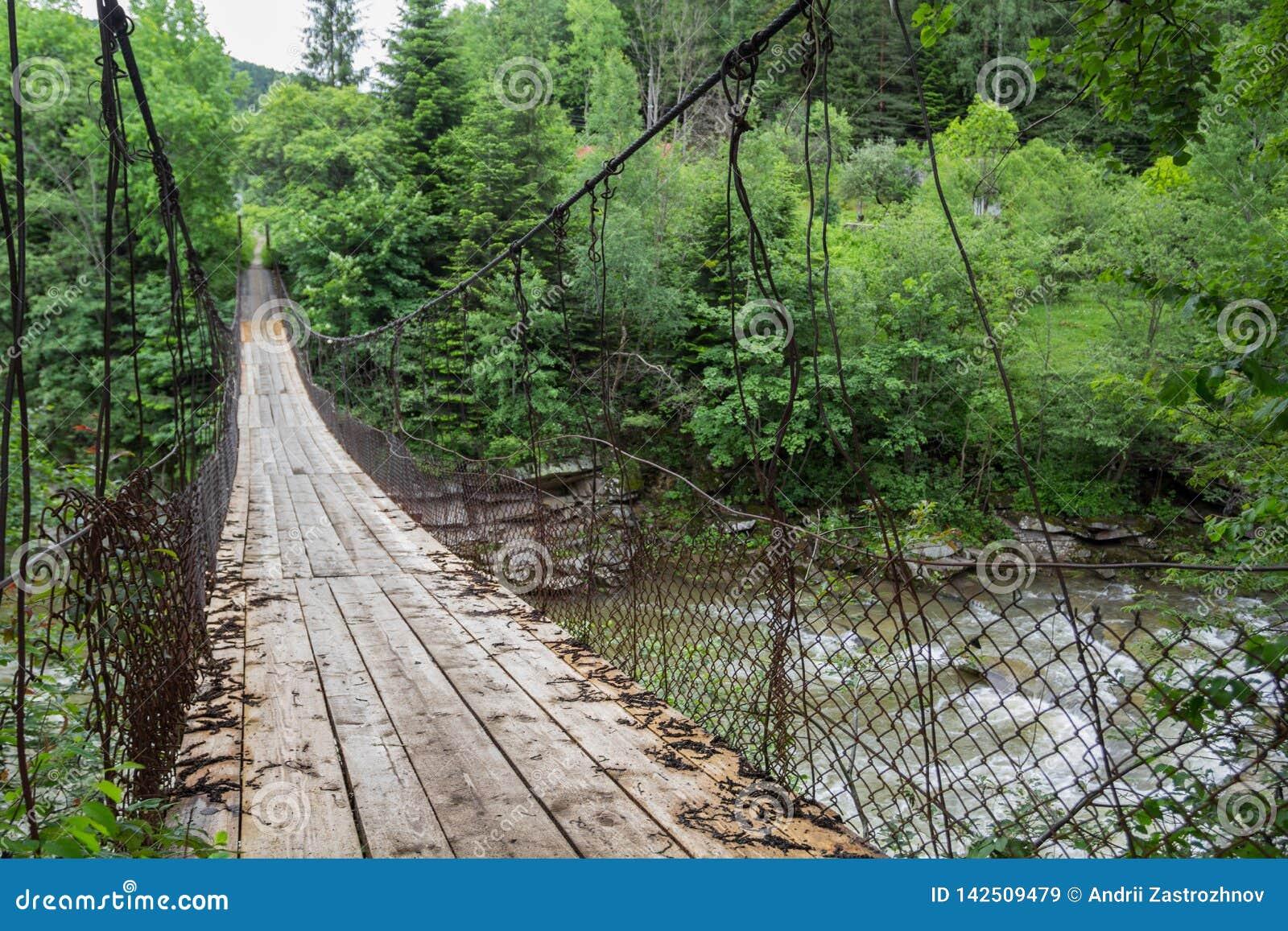 Alte Hängebrücke über dem Fluss im Wald