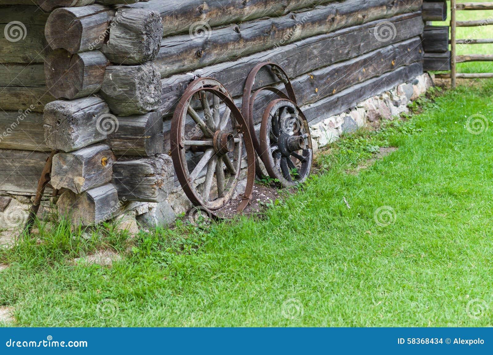 Alte hölzerne Räder des Warenkorbes auf Scheunenwand