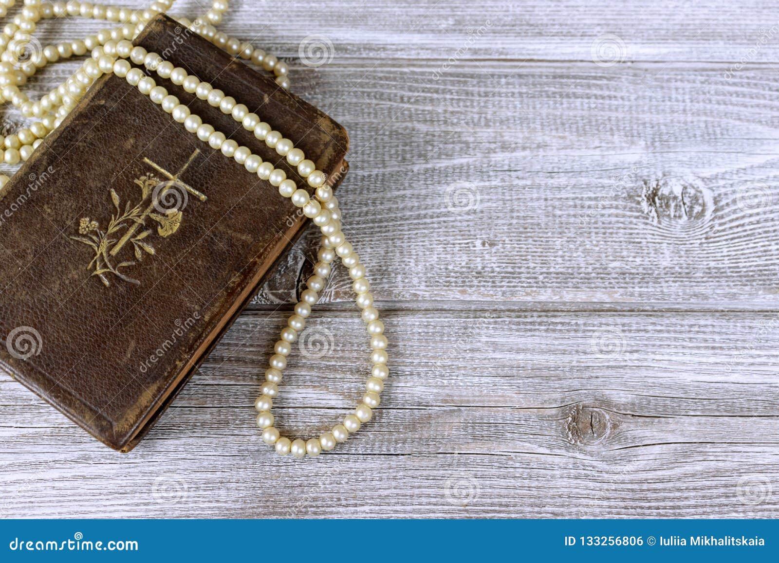 Alte heilige Bibel und Rosenkranzperlen auf rustikalem Holztisch