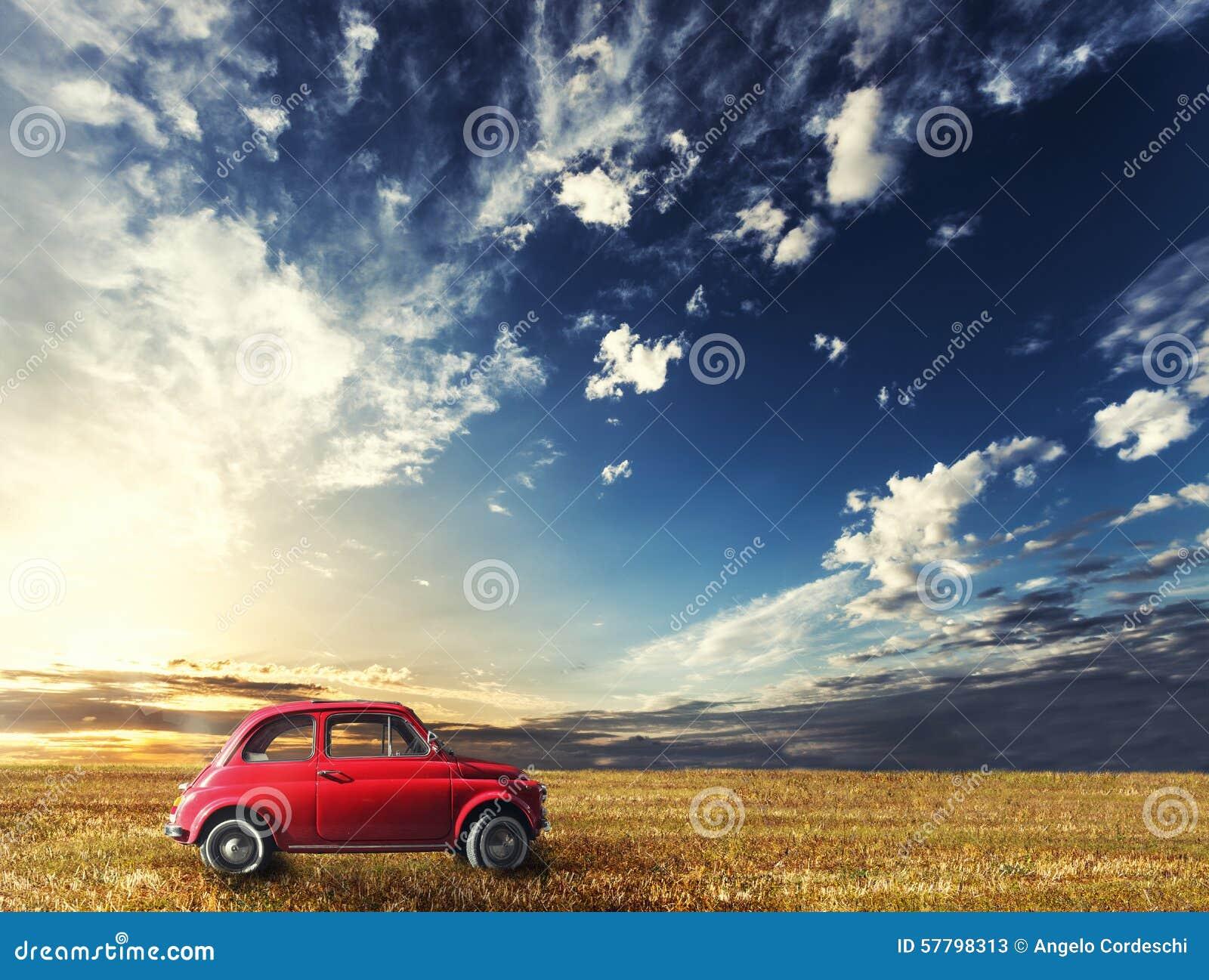 Alte kleine rote Auto Italienerweinlese Naturlandschaftssonnenuntergang