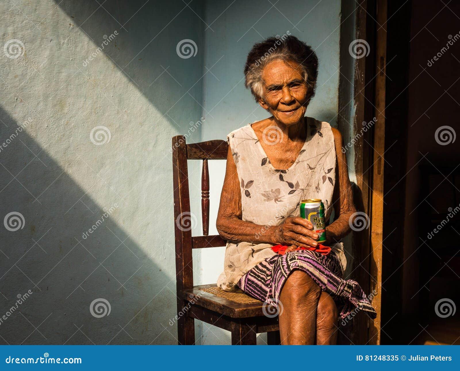 Alte kubanische Frau auf Stuhl ein Bier genießend