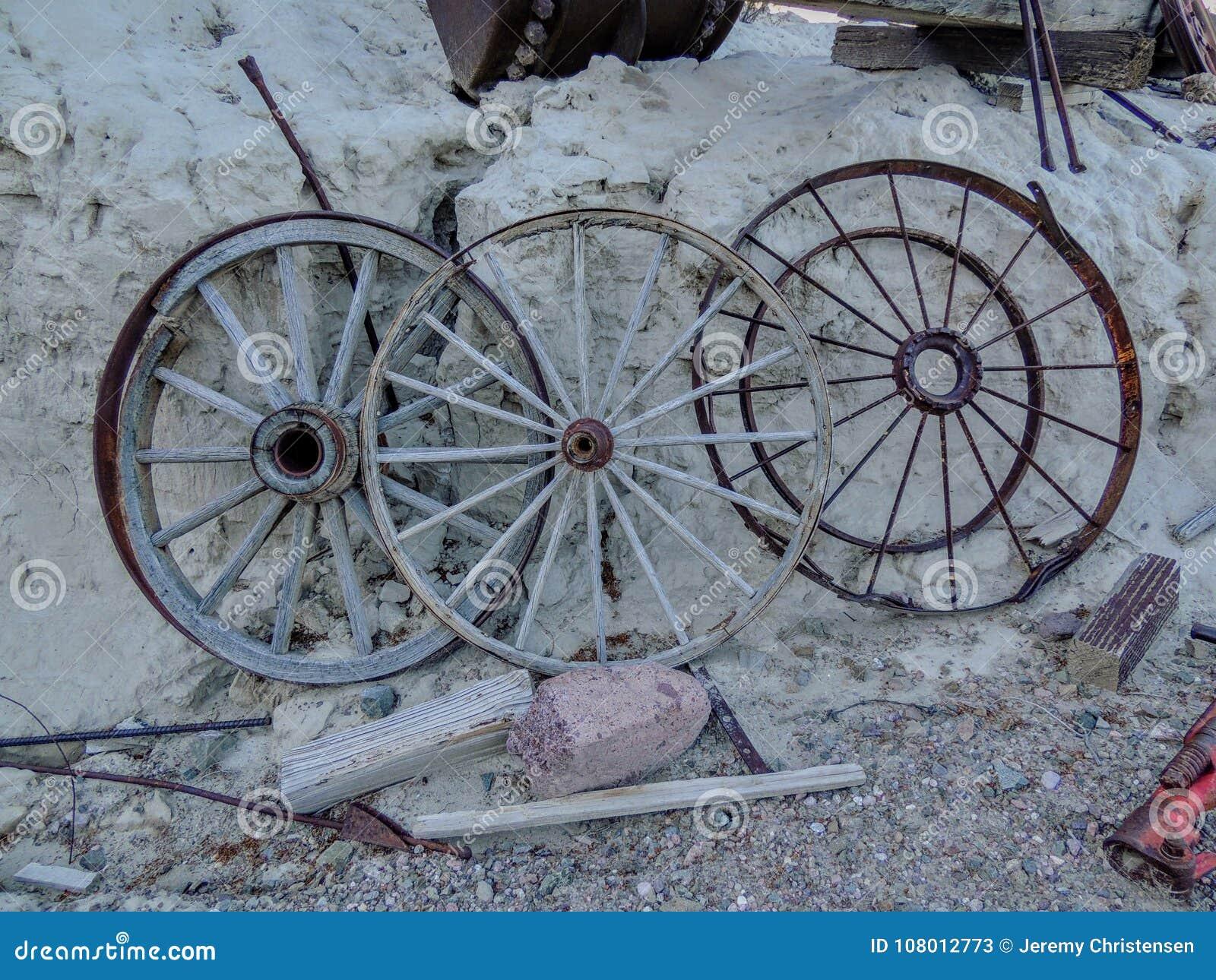Alte Metalllastwagenräder richteten entlang Bergwerksausrüstung in der Wüste in Arizona in einer verlassenen Geistbergbaustadt au