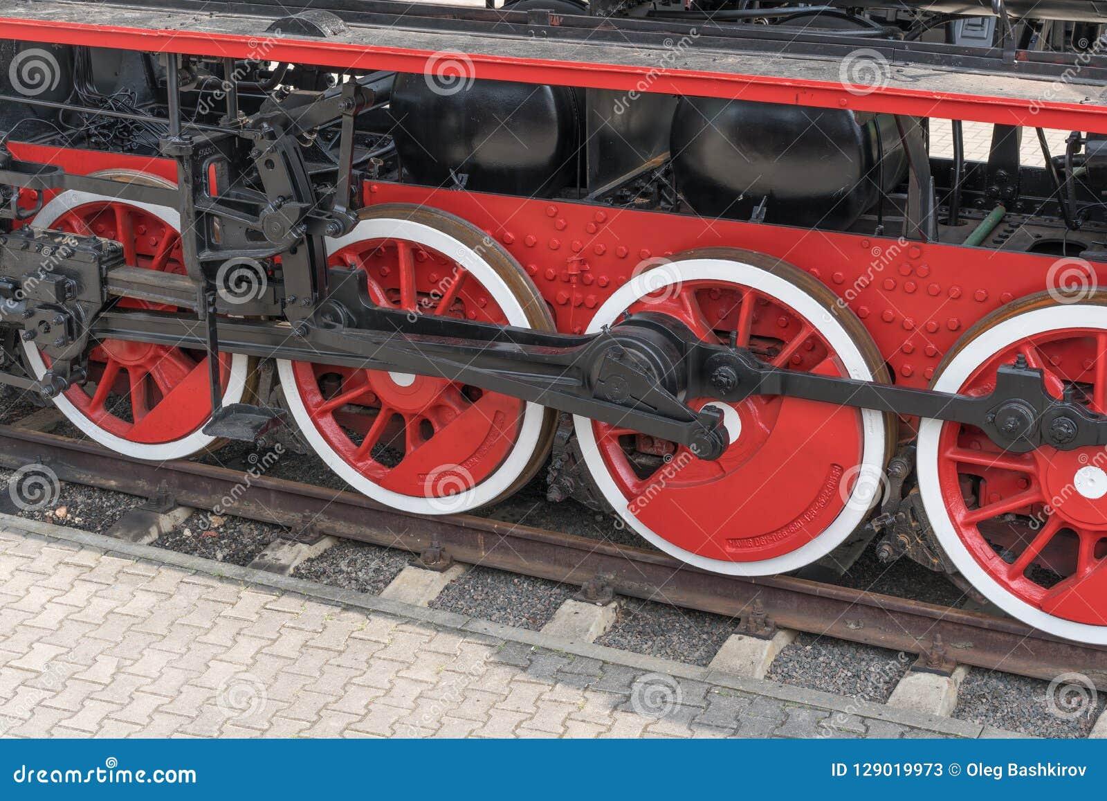 Alte nähernde Dampfzugräder, Nahaufnahme Schwarze und rote Räder Schienen und Lagerschwelle