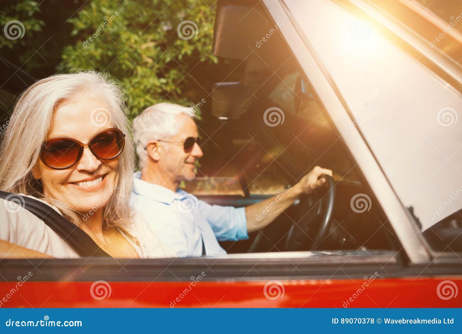 Alte Paare in einem Auto, das an der Kamera lächelt