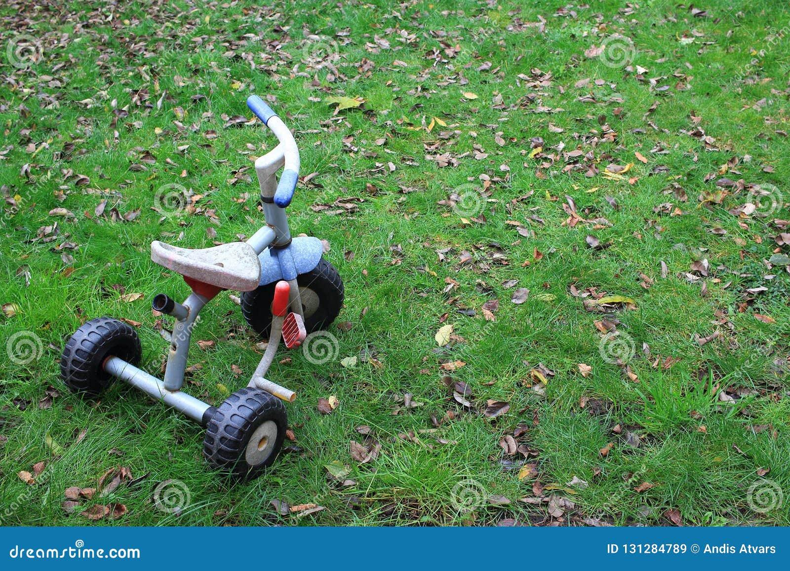 Alte Räder des Kinderdreirad drei fahren in den Garten rad