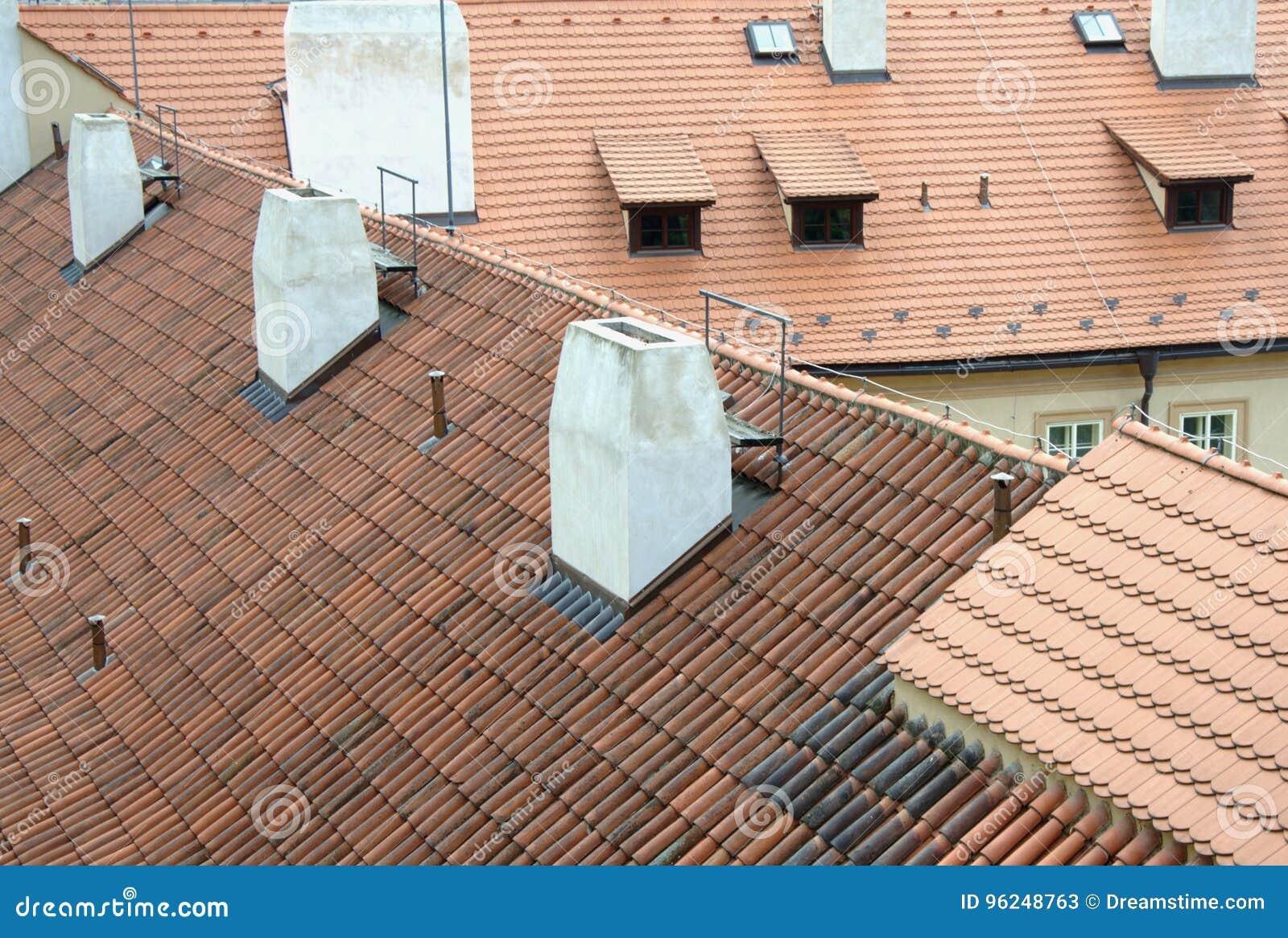 Alte rote Dachspitzen mit Fliesen und weißen Kaminen in Prag
