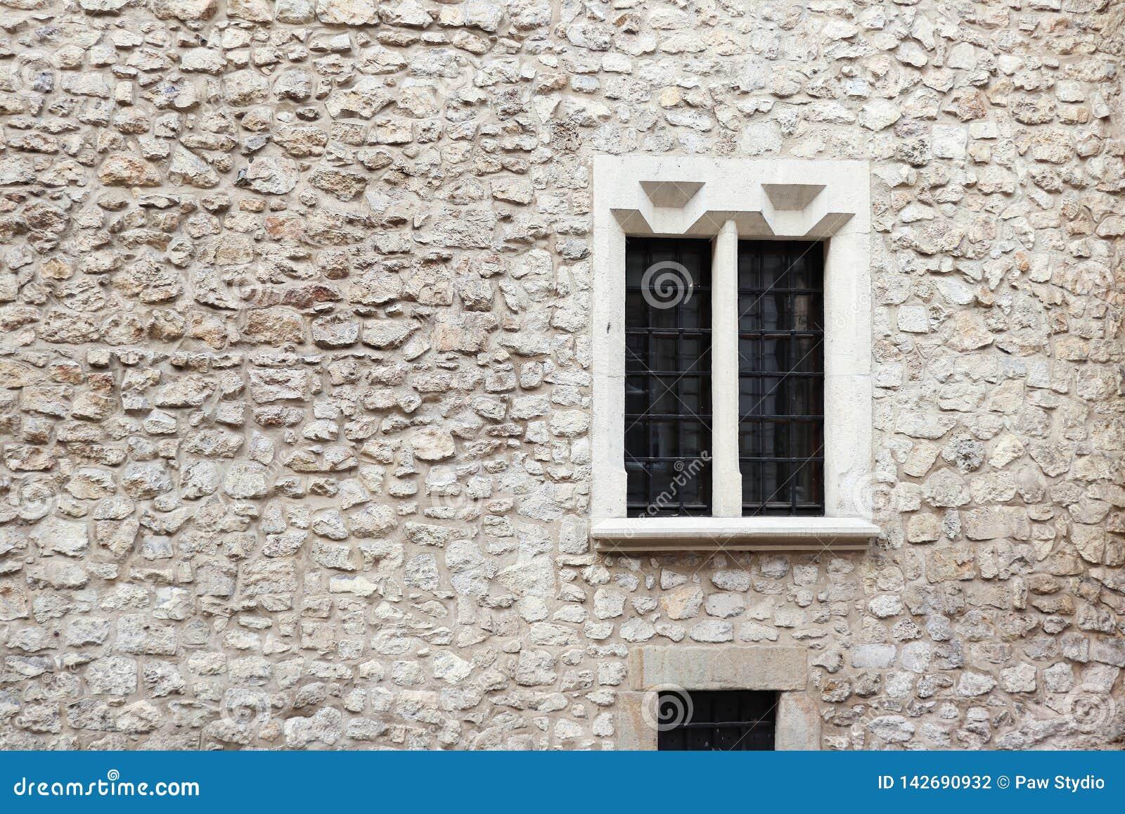 Alte Steinwand und Zement mit altem Fenster Sehr ausführlich und wirklich Krakau-Steinwand Bratpfannen auf den Fenstern Krakau-Ge