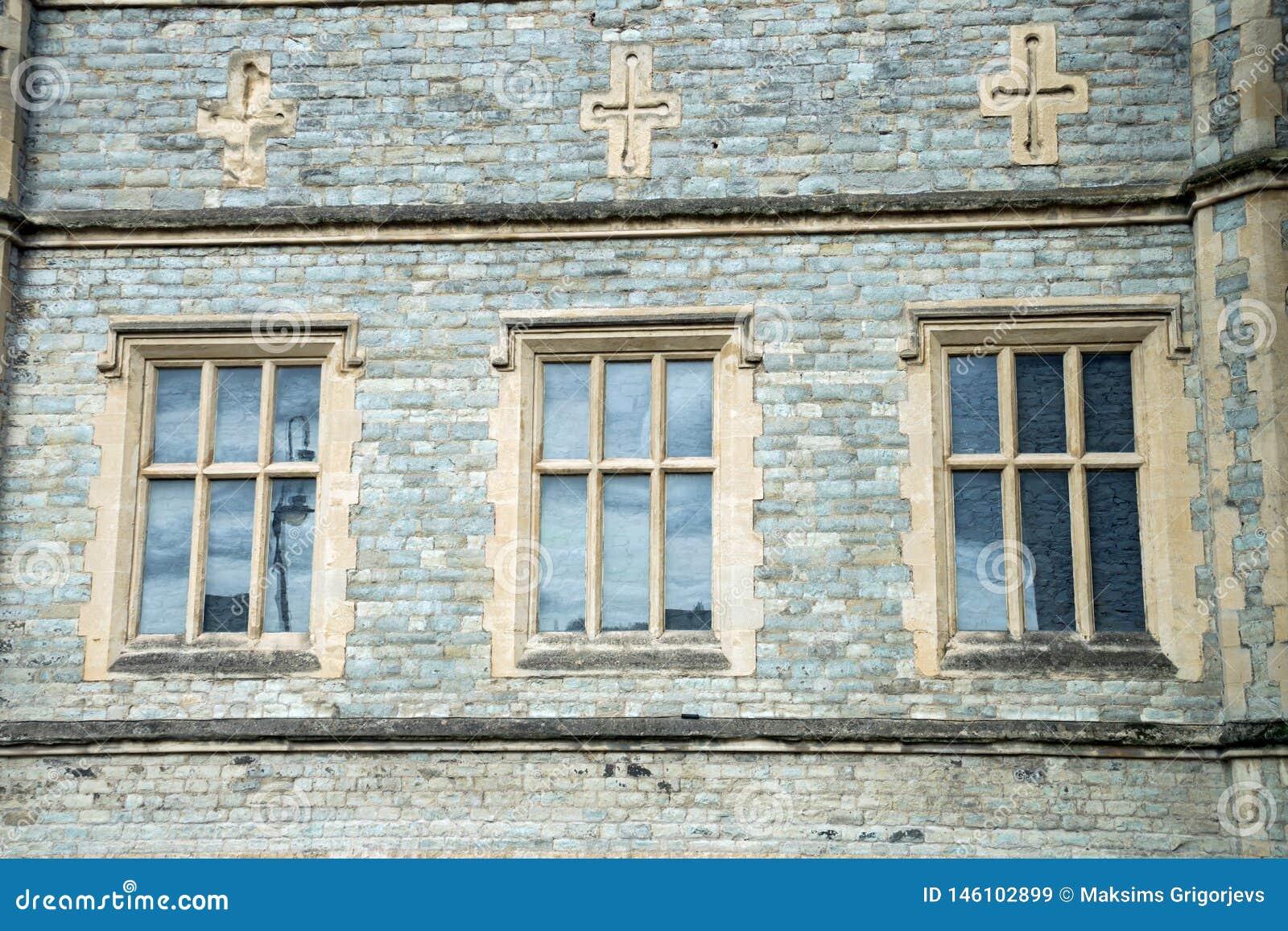 Alte traditionelle englische Architektur, drei Fenster und Kreuze oben