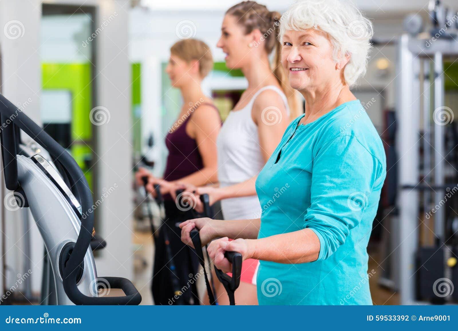 Alte und junge Leute auf Vibrationsplatten in der Turnhalle