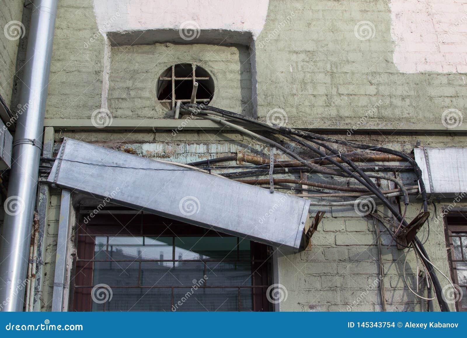 Alte verwirrte Drähte - elektrisch, Telefon, Antenne, Computer, Netz auf der Wand eines verfallenen Hauses mit unterschiedlichen