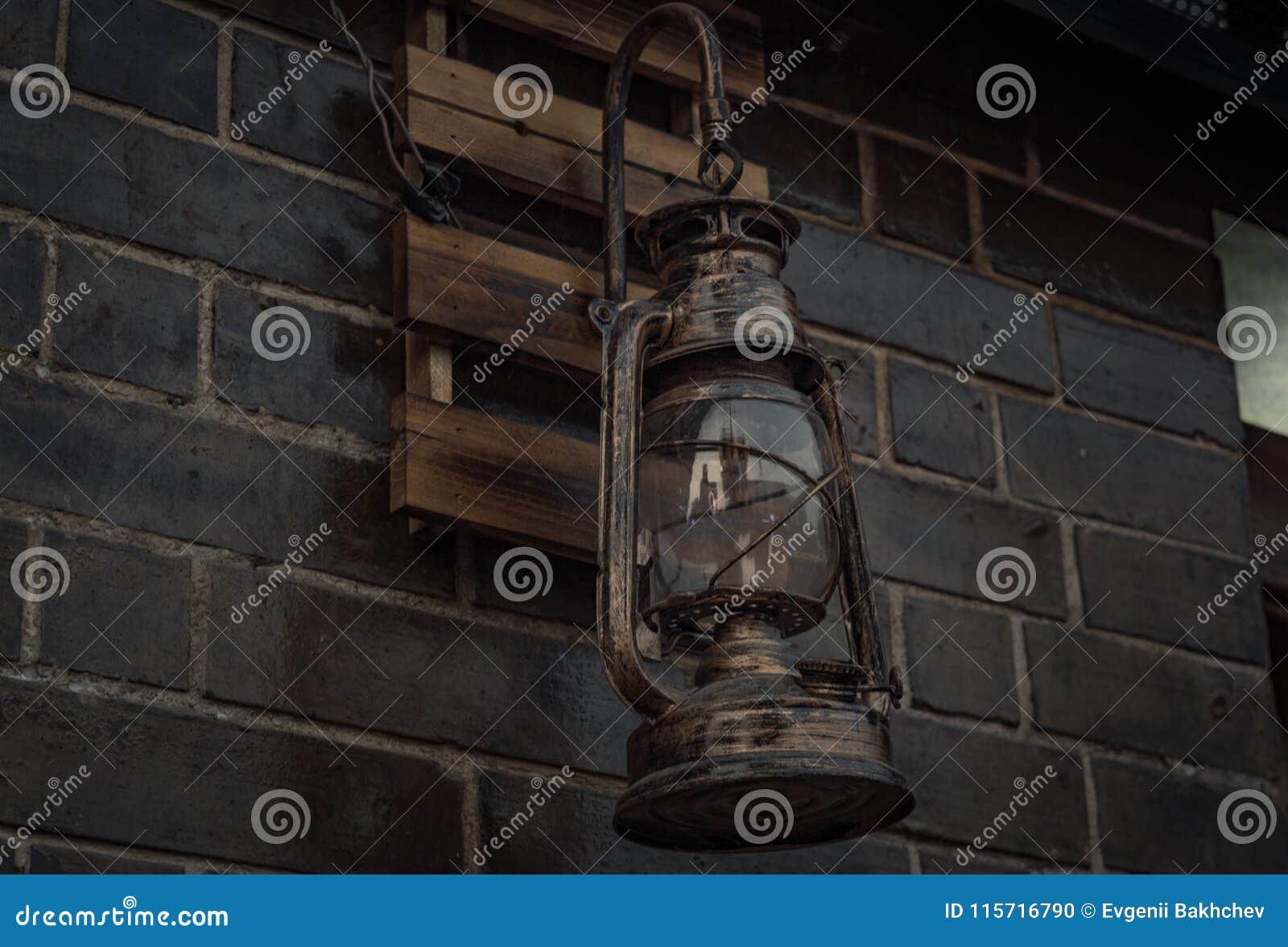 Alte Weinlesekerosin-Petroleumlaternelampe, die auf der Ziegelsteinwand hängt