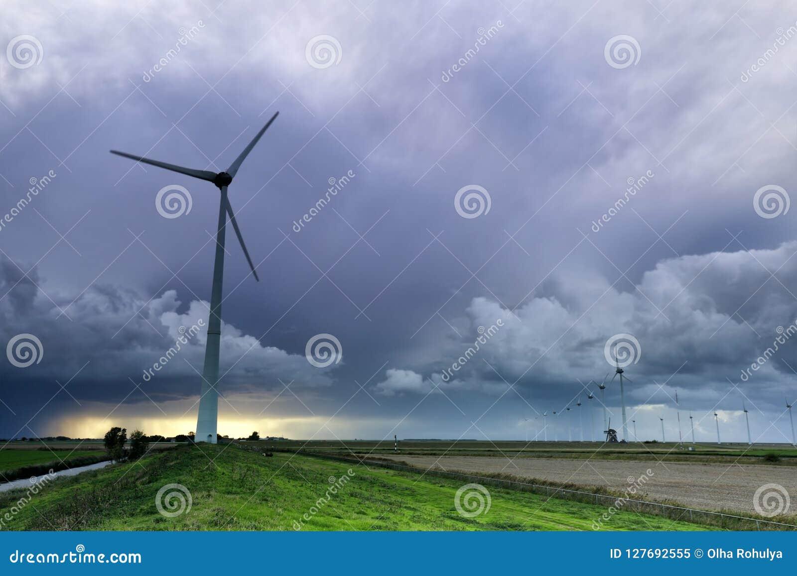 Alte Windmühle und moderne Turbinen am Sturm