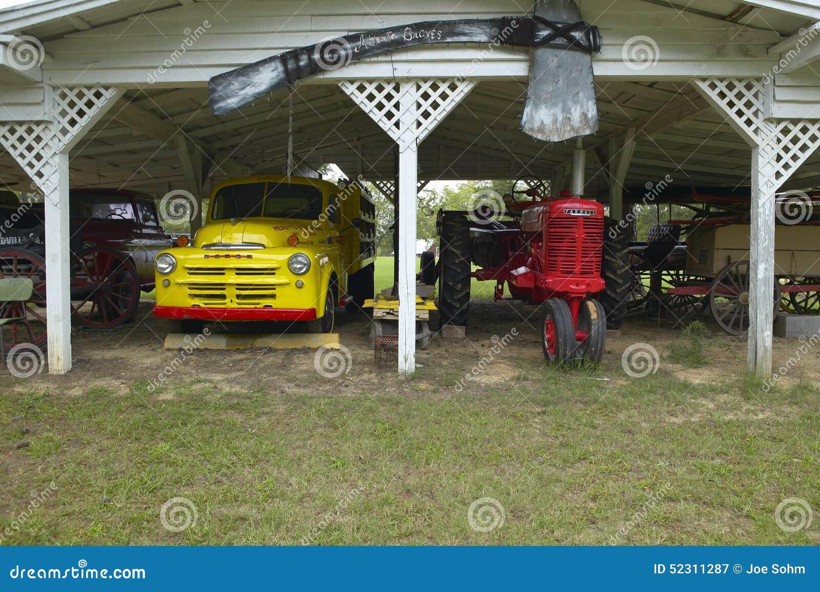 Alter dodge lkw und traktor in einer garage entlang