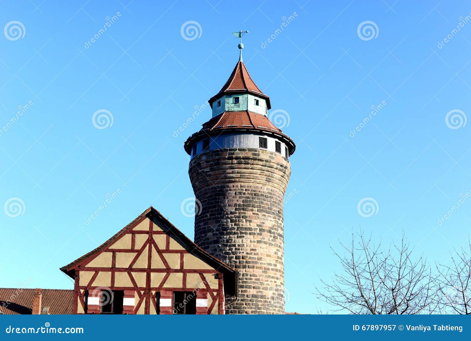 Alter historischer Ziegelstein blockiert Turm mit klarem blauem Himmel